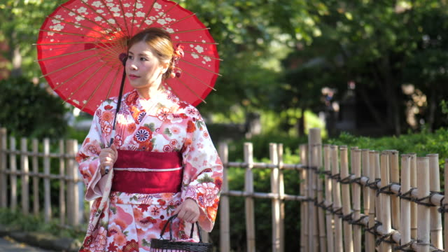 young female wearing kimono walking in the garden - kimono stock videos & royalty-free footage