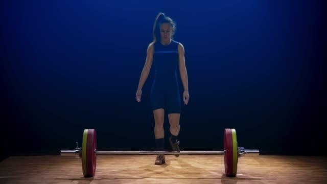 stockvideo's en b-roll-footage met jonge vrouwelijke gewichtheffer tillen van de barbell op een wedstrijd met een snatch lift - gewicht fysieke beschrijving