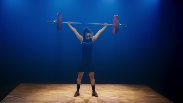 stockvideo's en b-roll-footage met ld jonge vrouwelijke gewichtheffer tillen van de barbell met de snatch lift op de concurrentie - gewicht fysieke beschrijving