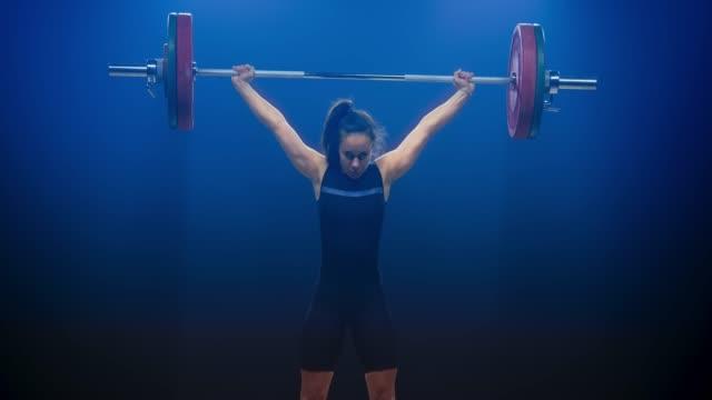 stockvideo's en b-roll-footage met jonge vrouwelijke gewichtheffer het uitvoeren van de snatch lift naar de halter lift op een wedstrijd - gewichten