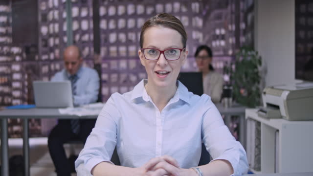 young female with glasses making a video call from the office - hands clasped stock videos & royalty-free footage