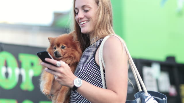 Young female with pet dog and smartphone