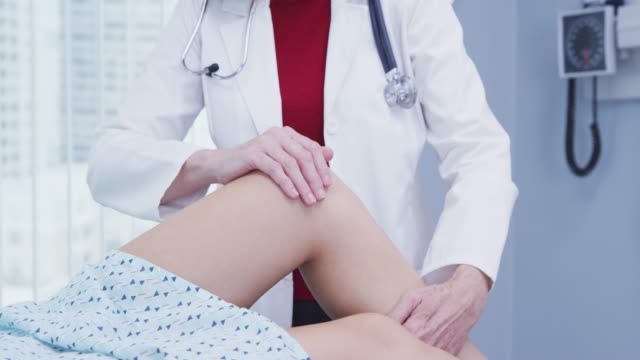 vídeos de stock, filmes e b-roll de young female woman having knee examined after sustaining injury in accident - physical injury