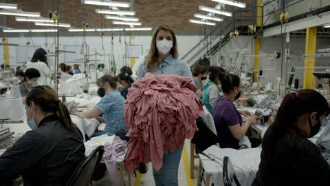 stockvideo's en b-roll-footage met jonge vrouwelijke arbeider bij een textielfabriek die onderaan de productielijn loopt die overhemden draagt - verwerkingsfabriek