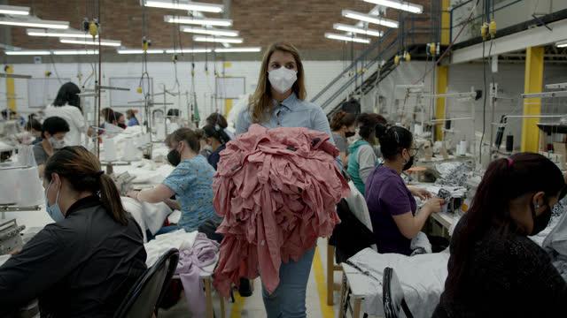vídeos y material grabado en eventos de stock de joven trabajadora en una fábrica textil caminando por la línea de producción llevando camisas - fábricas tradicionales