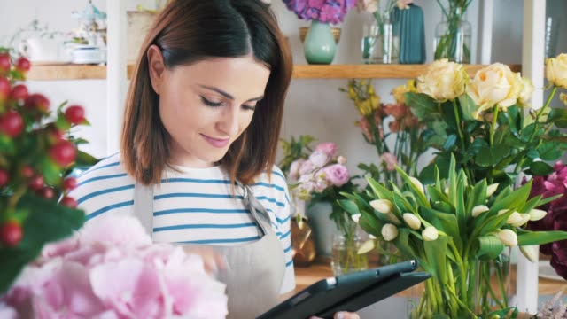 young female worker working in flower shop. - entrepreneur stock videos & royalty-free footage