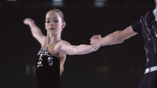 slo mo young figure skating pair holding hands during a spin - figure skating stock videos and b-roll footage