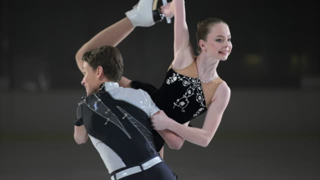 slo mo tu young figure skating pair performing - ice skating stock videos and b-roll footage