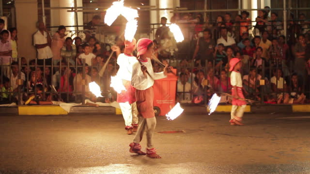 MS Young fire jugglers perform in Buddhist Festival or Procession 'Esala Perahera' (Festival of Tooth) AUDIO / Kandy, Central Province, Sri Lanka