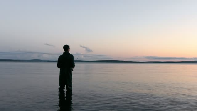 a young fisherman in a wader stands in the water of a calm large lake and reels a spinning reel while fishing alone in the evening - walking in water stock videos & royalty-free footage