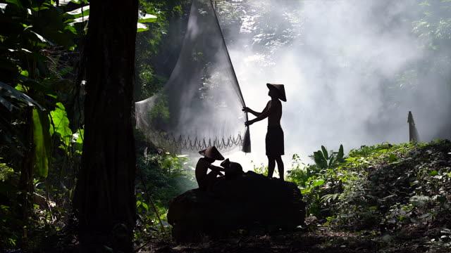 若い漁師は、背景としてジャングルの岩の上に釣りネットの前にネットを準備します。シルエット若い漁師屋外. 農業コンセプト - マダガスカル点の映像素材/bロール