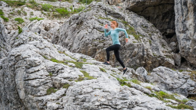 Young fit athletic woman running off the beaten path uphill a steep rocky mountain