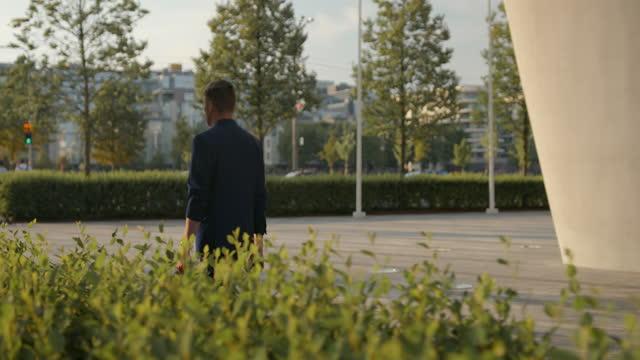 vídeos de stock, filmes e b-roll de um jovem empresário em forma em um terno azul passa pelos arbustos cortados em uma bela luz solar da noite contra a paisagem da cidade, vista de trás - vestuário de trabalho formal