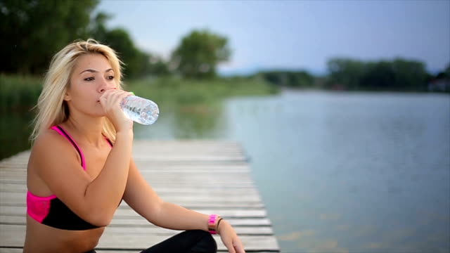young fit girl drinking water after training