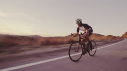Young Fit Man Cycling On Road Bike Outside At Sunset  Racing Downhill