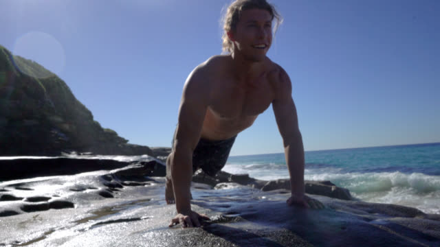 young fit man doing push ups looking very energetic next to the ocean - capelli biondi video stock e b–roll