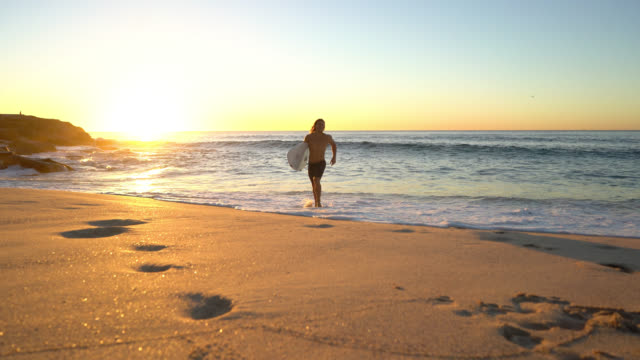 young fit man running back to the beach carrying his surfing board looking very happy - formazione rocciosa video stock e b–roll