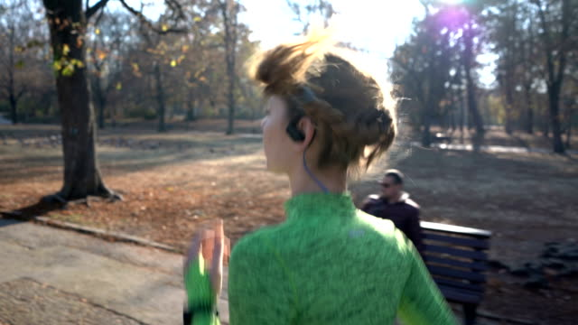 young fit woman running in the park - fitness tracker stock videos and b-roll footage