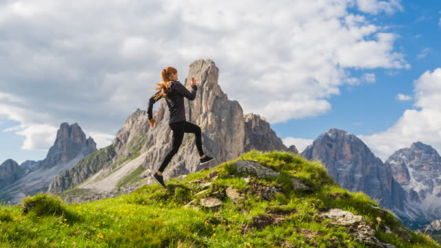 Young fit woman running on grassy meadow in Dolomites mountains, stopping at the edge, admiring the view