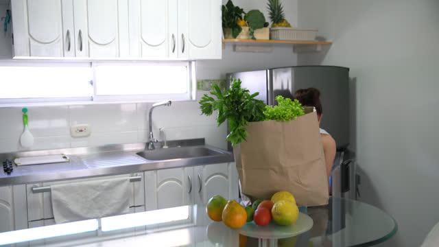 giovane donna in forma che spacchetta verdure e frutta da un sacchetto di carta e la organizza a casa - arrangiare video stock e b–roll