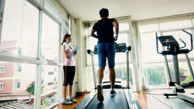 young  fitness  man running on a treadmill for exercising with woman trainer in gym, healthy lifestyle and cardio training concept - southeast asian ethnicity stock videos & royalty-free footage