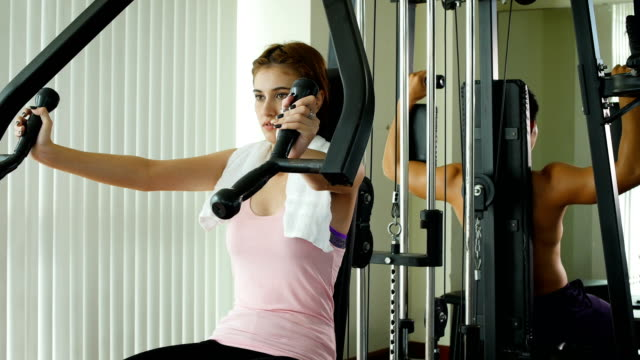 young fitness woman doing exercise with weights exercise-machine at the gym, fitness training concept - barechested bare chested stock videos and b-roll footage