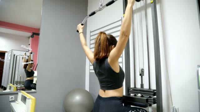 junge Fitness Frau führen Übung Übung-Maschine im Fitness-Studio