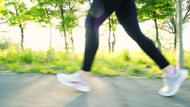 young fitness woman running on the road. - human leg stock videos and b-roll footage