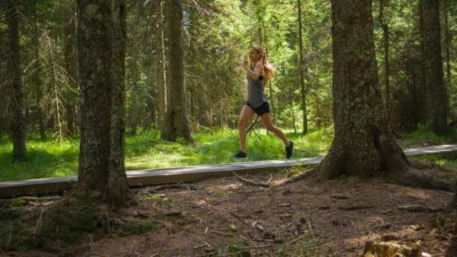 Young fitness woman staying healthy and getting fresh air while running through forest