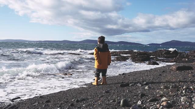 vidéos et rushes de jeune garçon de cinq ans jouant sur une plage et observant les vagues s'écraser sur le rivage - bottes
