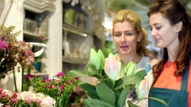 MS A young Florist advises a woman on a bunch of flowers in the shop