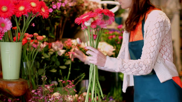 stockvideo's en b-roll-footage met ms young florist gathers flowers from the shop and smells them - ranonkel