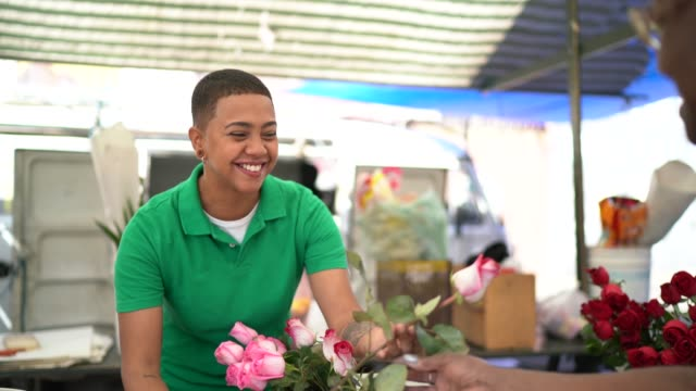 young florist selling a rose to client - market stall stock videos & royalty-free footage