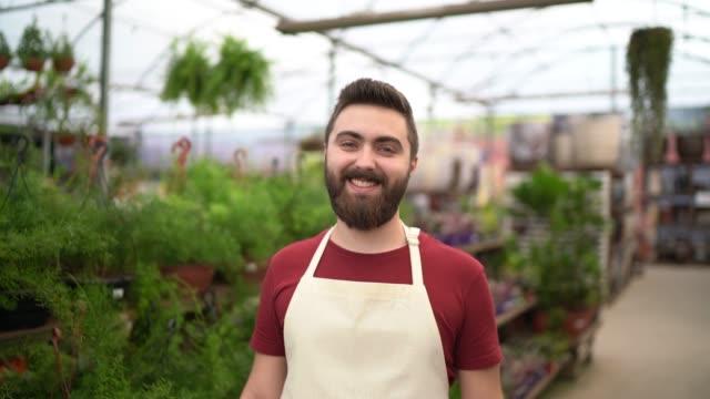 vídeos y material grabado en eventos de stock de joven florista trabajando en una pequeña floristería - pardo brasileño