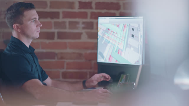 vidéos et rushes de young focused designer glances between two screens as he works on his computer - éléments de décoration intérieure