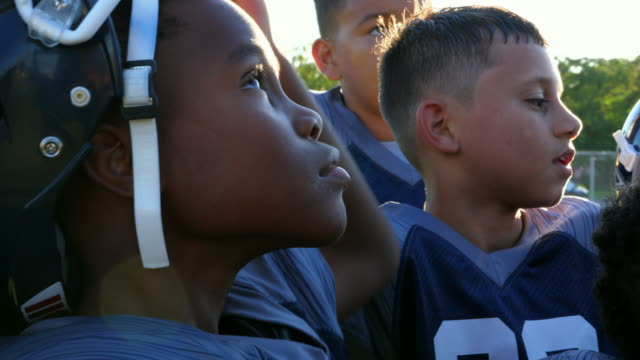 cu young football player looking up and listening to coach before football game - südliche bundesstaaten der usa stock-videos und b-roll-filmmaterial