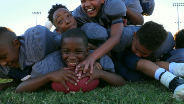 vídeos de stock e filmes b-roll de ms young football players tackling teammate on field after practice - tackling