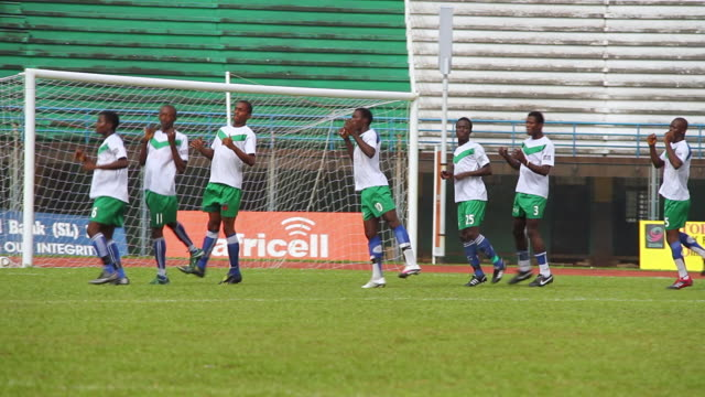 vidéos et rushes de ms ts young footballers going through series of training exercises and routines in warm up for match / freetown, sierra leone - s'entraîner