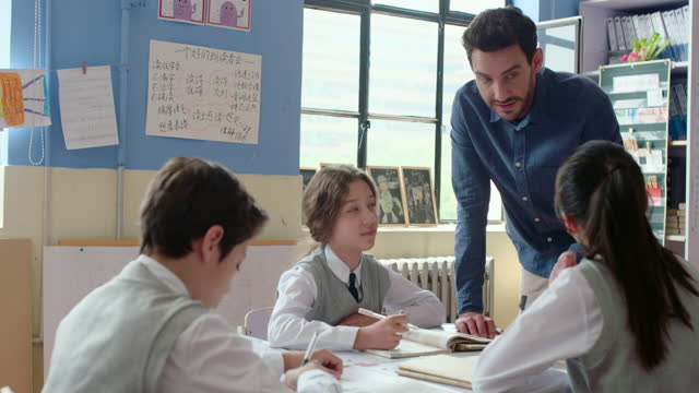 young foreign teacher helping students in class,4k - secondary school stock videos & royalty-free footage