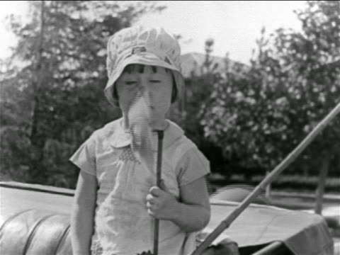 vídeos de stock e filmes b-roll de b/w 1927 young freckled girl (baby peggy) holding pinwheel turning fast + hitting her nose / feature - banco do passageiro