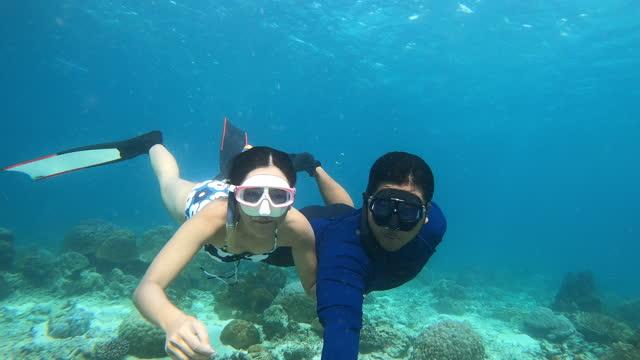 vídeos y material grabado en eventos de stock de 4k joven pareja de buceadores libres usar aletas largas y máscara de snorkel selfie shot buceo en aguas cristalinas frente a hermoso arrecife de coral y peces en el océano - buceo con equipo