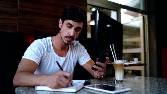 young freelancer taking notes at cafe - author stock videos & royalty-free footage