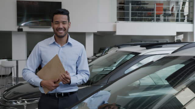 young friendly salesman at a car dealership holding a clipboard facing camera smiling - sales occupation stock videos & royalty-free footage