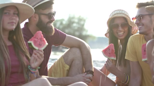 young friends eating watermelon on beach - picnic stock videos & royalty-free footage
