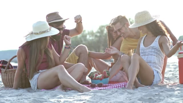 vídeos de stock e filmes b-roll de young friends eating watermelon on beach - picnic