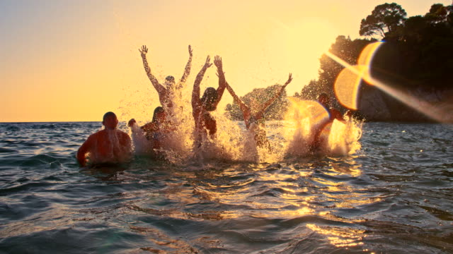 stockvideo's en b-roll-footage met slo mo young friends jumping out of the sea - friendship