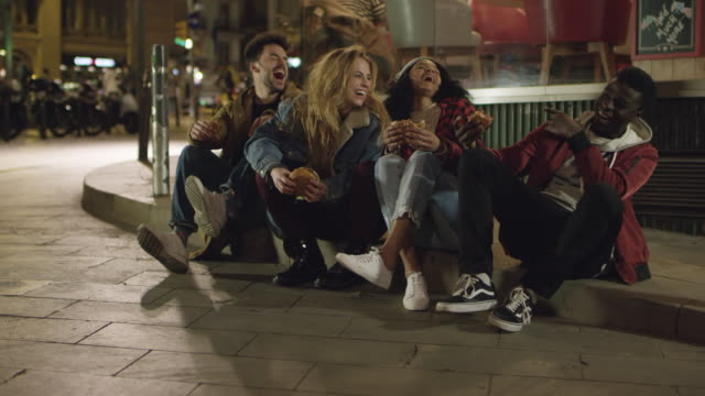 young friends laughing while sitting on sidewalk - 18 19 years stock videos & royalty-free footage