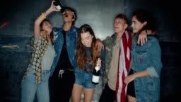 Young friends partying together with champagne and an American flag