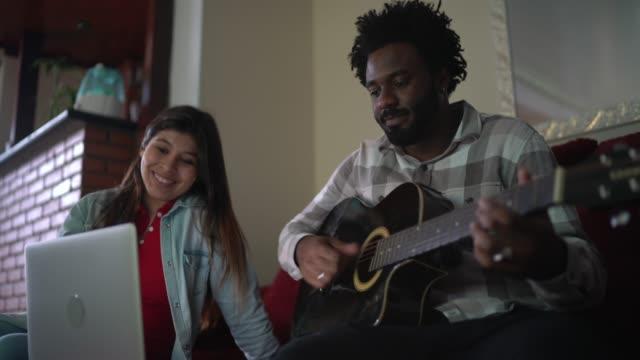 vídeos de stock, filmes e b-roll de jovens amigos tocando violão na frente de um laptop - performance