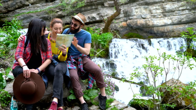 Young friends reading map while resting at the river bank